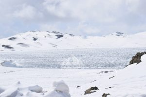 Frozen Sheosar lake starting to melt in June with snow covered mountains in the background