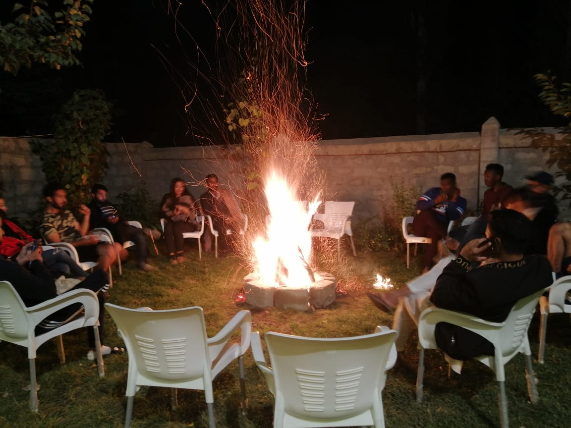 Bonfire in the garden of hotel in hunza with tourists around it