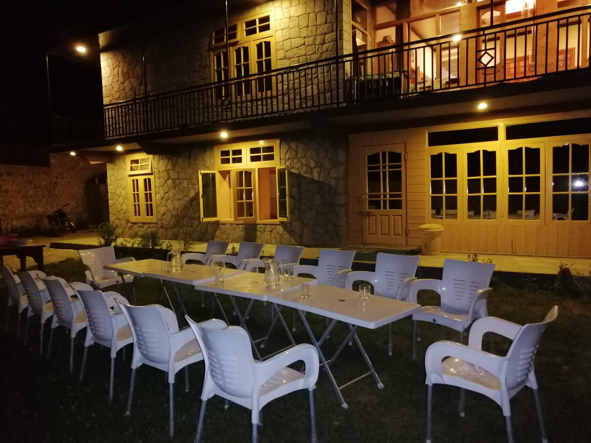Hotel in hunza at night with tables and chairs