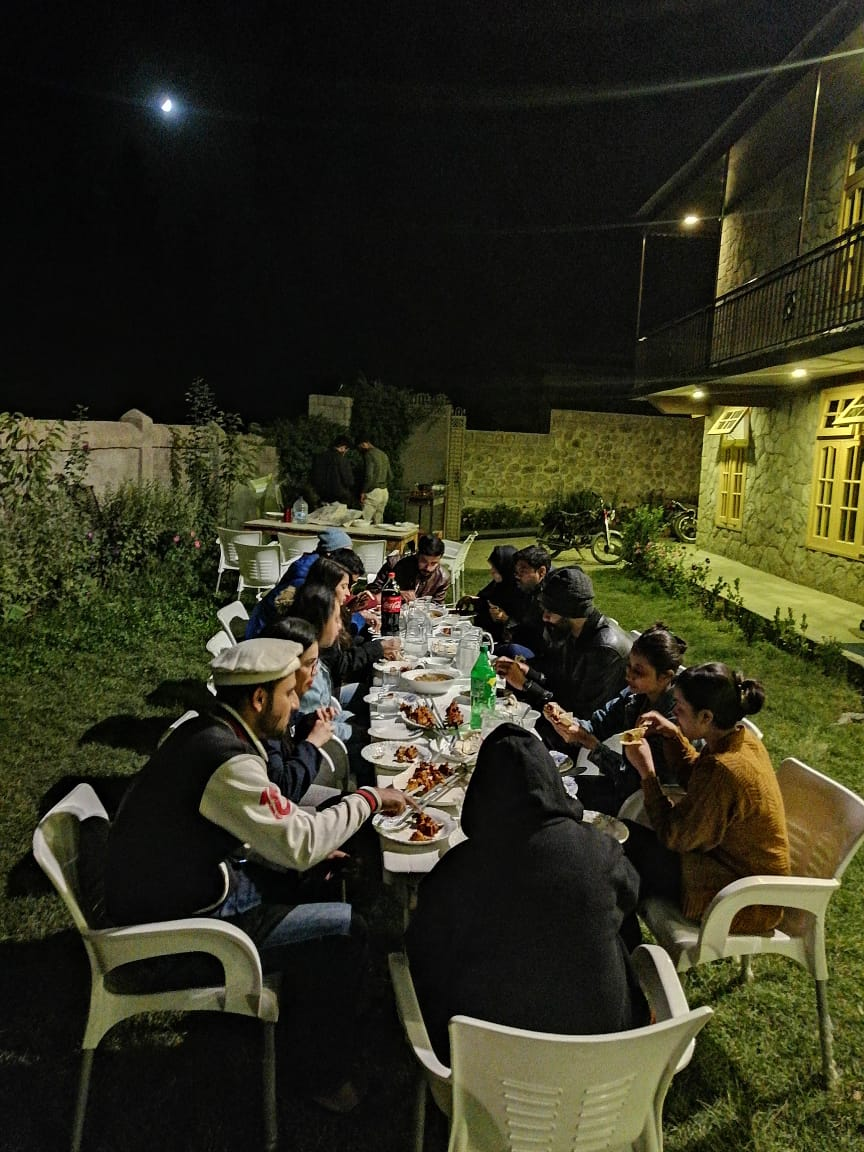 Tourists having dinner in garden of hotel in hunza